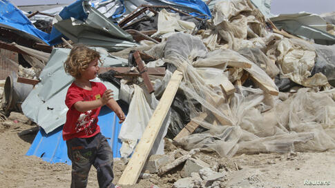 A Palestinian girl cries as she walks past her family's house after it was demolished by Israeli bulldozers in Om Ajaj village, north of the West Bank city of Jericho.