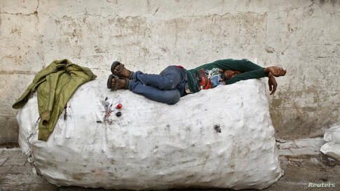 A rag picker takes a nap on a sack filled with used plastic bottles, on the side of a road in New Delhi, India.