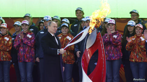Russian President Vladimir Putin holds a lighted Olympic torch during a ceremony to mark the start of the Sochi 2014 Winter Olympic torch relay, Moscow, Oct. 6, 2013.