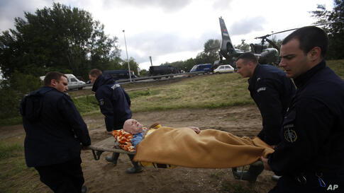 Police officers carry a man from a military helicopter during flood evacuation from Obrenovac, Serbia, May 17, 2014.