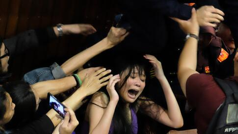 A protester shout as police officers try to remove the chairs rrom the entrance of the Taiwanese Parliament in Taipei occupied by activists to protest against moves by the ruling Kuomintang party to ratify a contentious trade agreement with Chinain.