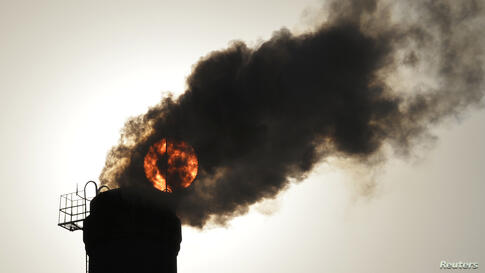 The sun is seen behind smoke billowing from a chimney of a heating plant in Taiyuan, Shanxi province, China.