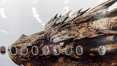 """An image of the dragon Smaug from Peter Jackson's Hobbit trilogy is shown on the side of an Air New Zealand plane in Auckland, New Zealand. The image was unveiled to celebrate the premiere of """"The Hobbit: The Desolation of Smaug,"""" which screens in Los ..."""