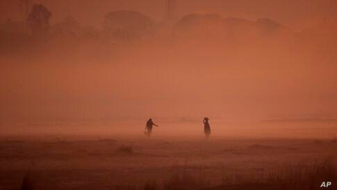 Villagers walk home carrying water collected from the Kuakhai River on a foggy morning in Bhubaneswar, India.