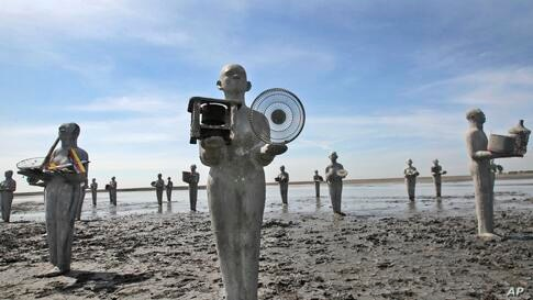 """Statues, called """"Survivors"""" created by Indonesian artist Dadang Christanto, are erected at the site that has been overwhelmed by mud oozing from a mud volcano, in Porong, East Java, Indonesia. The statues were installed to commemorate the 8th year sinc..."""