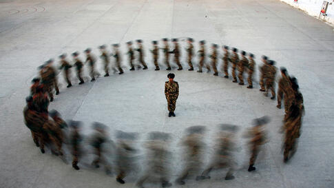 Dec. 29: A commander watches as recruits of paramilitary police run in a circle during a training at a military base in Hami, Xinjiang Uighur Autonomous Region. December 29, 2010. (Reuters)