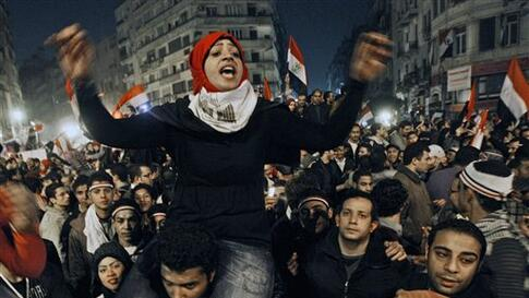 An Egyptian woman celebrates with other people after President Hosni Mubarak resigned and handed power to the military at Tahrir square, in Cairo, Egypt, Friday, Feb. 11, 2011. Egypt exploded with joy, tears, and relief after pro-democracy protesters brou