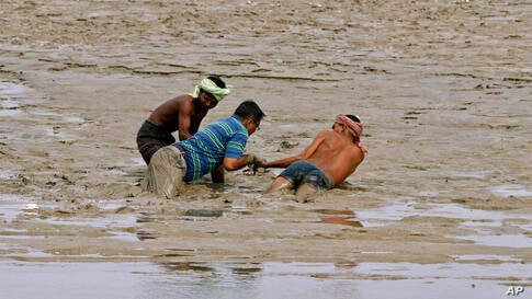Indian boatmen pull out a man trapped in a swamp after heavy rainfall at Sangam in Allahabad.