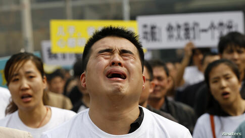 A family member of a passenger on board Malaysia Airlines MH370 cries as he shouts slogans during a protest in front of the Malaysian embassy in Beijing, China.