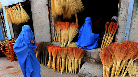 Afghan shoppers look for brooms at a roadside shop in Herat.