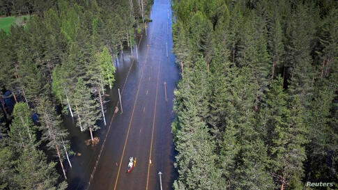 Two men paddle in a canoe on a flooded road in Trysil, southeast Norway. Rain and melted snow have increased the water level in the river Trysilelva.
