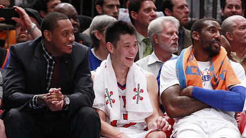 New York Knicks' Jeremy Lin, center, talks with teammates Carmelo Anthony, left, and Amare Stoudemire, right, during an NBA basketball game against the Sacramento Kings, February. 15, 2012, in New York. The Knicks won the game 100-85. (AP)