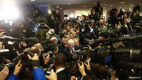 Freed Russian former oil tycoon Mikhail Khodorkovsky (C) arrives for his news conference in the Museum Haus am Checkpoint Charlie in Berlin, Germany. Khodorkovsky, pardoned by Russian President Vladimir Putin after 10 years in jail, said in remarks tha...