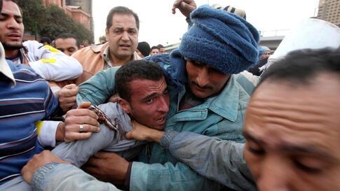 February 3: A pro-Mubarak supporter apprehended by opposition demonstrators is led away during rioting.  (Suhaib Salem/Reuters)