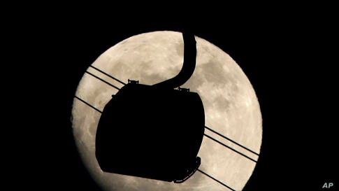 A gondola used to transport people to the biathlon and cross country skiing venues is silhouetted against the rising moon in Krasnaya Polyana, Russia.