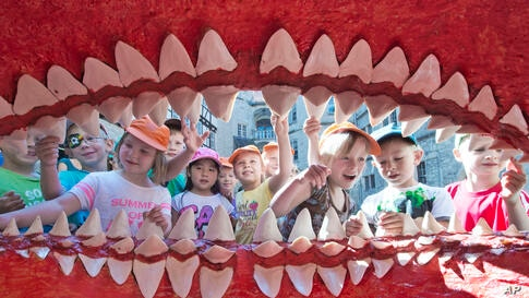 Children of a kindergarten admire the giant mouth of a primeval Megalodon shark model at the Natural History Museum in Schleusingen, central Germany.