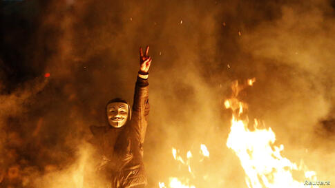 An anti-government protester wearing a Guy Fawkes mask gestures behind a barricade that they set on fire during a demonstration in Ankara, Turkey, Mar. 12, 2014. Riot police clashed with demonstrators in several Turkish cities for a second day as mourn...