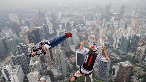 Base jumper Jean-Philippe Marie Teffaud, left, and his team mate Frederic Yves Fugen of France leap from the 300-meter Open Deck of the Malaysia's landmark Kuala Lumpur Tower during the International Tower Jump in Kuala Lumpur.
