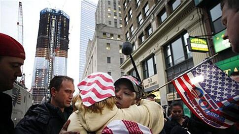 Dionne Layne, facing camera, hugs Mary Power as they react to the news of the death of Osama bin Laden, Monday, May 2, 2011 in New York. At left is the rising tower, 1 World Trade Center, also known as the Freedom Tower. (AP Photo/Mark Lennihan)