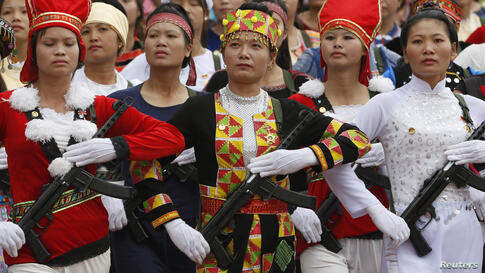 Vietnamese female militants, dressed in ethnic minorities costumes, hold WWII-era submachineguns while marching during the 60th anniversary celebrations of the Dien Bien Phu battle in the historic city. Viet Minh forces overran the French garrison in D...