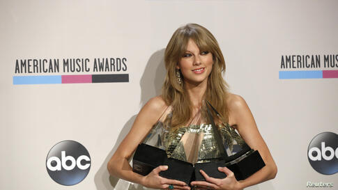 "Musician Taylor Swift poses backstage with her awards for artist of the year, favorite country artist - female, favorite country album for ""Red"" and favorite female pop/rock at the 41st American Music Awards in Los Angeles, California, Nov. 24, 2013."