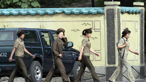 Female North Korean soldiers walk along the banks of the Yalu River near the town of Sinuiju, opposite the Chinese border city of Dandong.