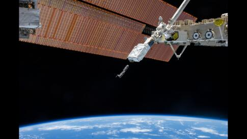 The Small Satellite Orbital Deployer (SSOD), in the grasp of the Kibo laboratory robotic arm, is photographed by an Expedition 38 crew member on the International Space Station as it deploys a set of NanoRacks CubeSats.