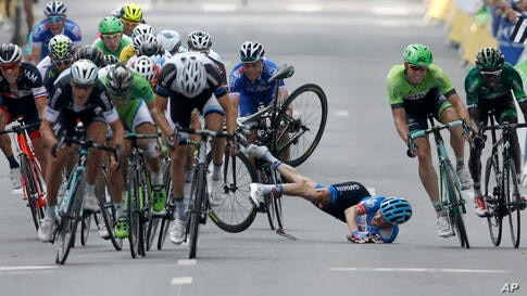 Andrew Talansky of the U.S. crashes as the pack with stage winner Italy's Matteo Trentin, foreground left, sprints towards the finish line during the 7th stage of the Tour de France.