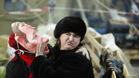 A pro-European integration protester wearing a mask depicting Russian President Vladimir Putin tries to kiss a woman during a rally in Independence square in Kyiv, Ukraine.