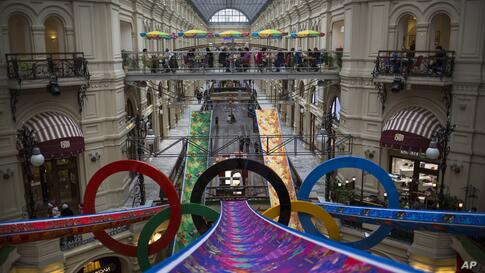 Visitors walk inside the GUM department store decorated with Olympic rings in Moscow, Russia, Feb. 12, 2014.
