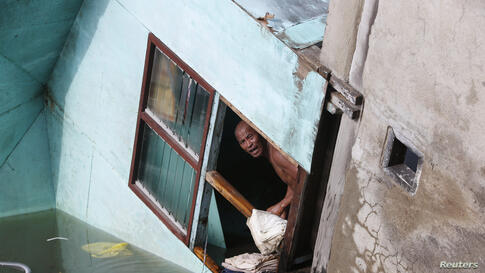 A resident looks out from a window of his family's home, which fell into a river in Buenavista, Bohol a day after an earthquake hit central Philippines. The death toll from the earthquake rose to 107, as rescuers dug through the rubble of a church and ...