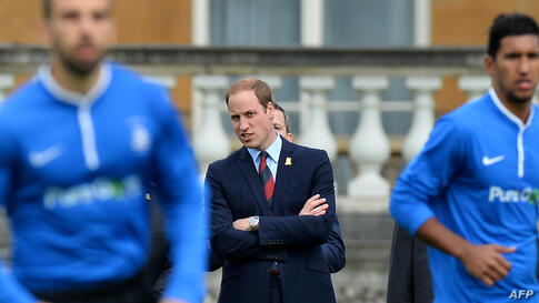 Britains Prince William looks on as Polytechnic FC (In Blue) play Civil Service FC in a Southern Amateur League football match in the grounds of Buckingham Palace, in central London.