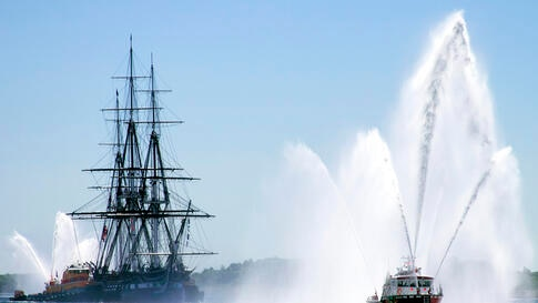 USS Constitution is escorted by a Massport Fire Rescue boat during her first turnaround cruise of 2013 in Boston, Massachusetts.