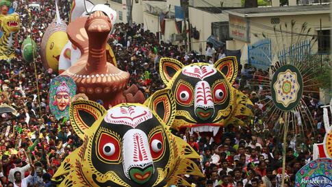 People carry masks and different animal floats down a street during celebrations on Pohela Boishakh, the first day of the Bengali new year in Dhaka.