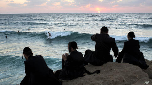Ultra-Orthodox Jewish men watch Israeli surfers during the Jewish holiday of Sukkot in the southern Israeli port city of Ashdod, Sept. 23, 2013.