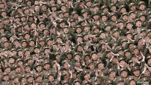 Soldiers of KPA Units 966, 462, 101, 489, who took part in building the workers' hostel of Kim Jong Suk Pyongyang Textile Mill, applaud during a photo session with North Korean leader Kim Jong Un in this undated photo released by North Korea's Korean C...
