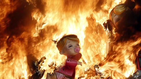 """Satirical sculptures burn during the traditional Fallas festival in Valencia, Spain, Mar. 19, 2014. Every year the city of Valencia celebrates the ancient """"Las Fallas"""" fiesta, a noisy week that is full of fireworks and processions in honor of Saint Jos..."""
