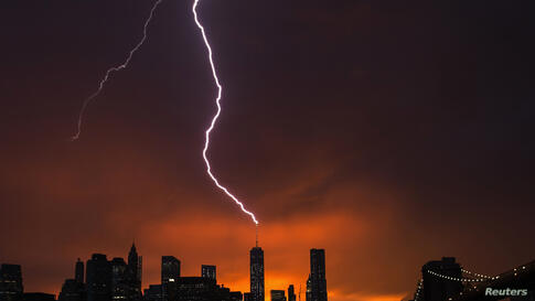 Lightning strikes One World Trade Center in Manhattan, New York, as the sun sets behind the city after a summer storm, July 2, 2014.