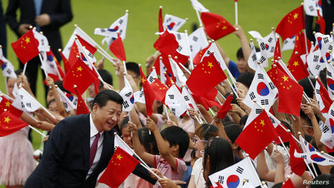 Chinese President Xi Jinping greets children waving Chinese and South Korean national flags during a welcoming ceremony at the presidential Blue House in Seoul, South Korea.
