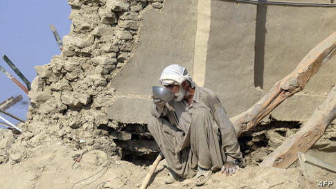 A Pakistani earthquake survivor drinks water at his collapsed mud house in the Dhall Bedi Peerander area of the earthquake-devastated district of Awaran. Tens of thousands of survivors of earthquake waited for help in soaring temperatures as the death ...