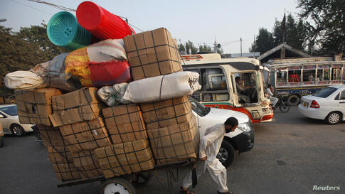 A laborer pulls a cart loaded with supplies while heading to a nearby market in Karachi, Pakistan.