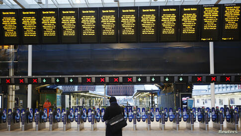 A man stands alone at London Bridge Station after numerous trains were cancelled due to storms. Disrupted transport networks and power outages wreaked havoc in Britain and France, one of the busiest travel and shopping days of the year just before Chri...