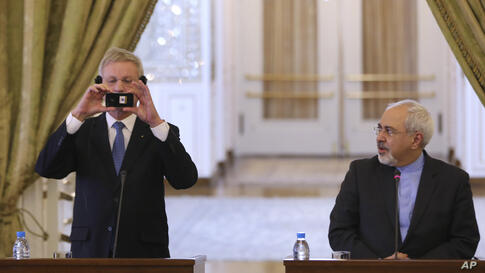 Swedish Foreign Minister Carl Bildt, left, takes picture with his mobile as his Iranian counterpart Mohammad Javad Zarif looks at him during their news briefing in Tehran, Iran.