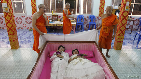 Groom Tanapatpurin Samangnitit and his bride Sunantaluk Kongkoon, lie in a coffin during a wedding ceremony at Wat Takien temple in Nonthaburi province, on the outskirts of Bangkok, Thailand. Seven couples laid in the pink coffin during the wedding cer...