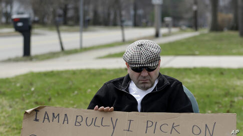 Edmond Aviv sits on a street corner holding a sign in South Euclid, Ohio declaring he's a bully, a requirement of his sentence because he was accused of harassing a neighbor and her disabled children for the past 15 years, April 13, 2014.