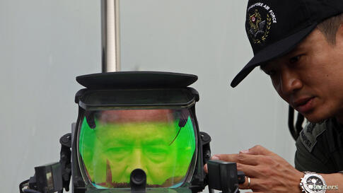 Brunei's Sultan Hassanal Bolkiah looks into the heads-up display of a Republic of Singapore Air Force Lockheed F16-D Fighting Falcon at the Singapore Airshow.