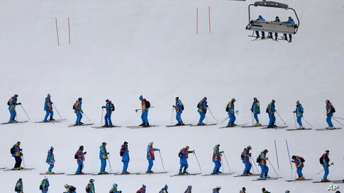 Workers groom the women's downhill course at the Rosa Khutor Alpine center at the 2014 Winter Olympics, Feb. 14, 2014.