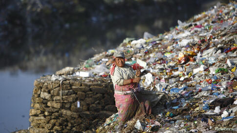 A woman searches for recyclable waste at a dump site on the banks of the Bagmati River in Kathmandu, Nepal.