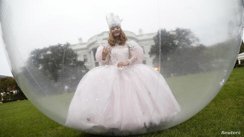 """An actress in a """"good witch"""" costume walks around ahead of a Halloween reception for children on the South Lawn at the White House in Washington, D.C., Oct. 31, 2013."""