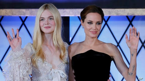 """Actresses Angelina Jolie, right, and Elle Fanning wave during the premiere of """"Maleficent"""" in Tokyo, Japan."""